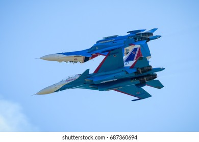 """Zhukovsky, Russia - July 21, 2017: Aerobatic display team """"Russian Knights"""" on Su-30SM performs a trick at MAKS. Russian air force fighters are flying in blue sky. Dangerous approach of two aircraft."""