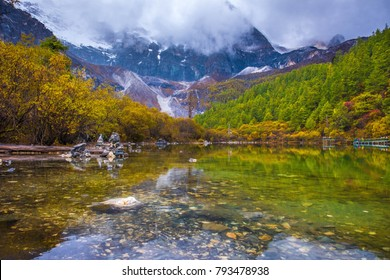 Zhuoma La lake with Mt. Xiannairi, the highest peak in Daocheng Country (6,032m.), one of three holy mountains in Yading Nature Reserve during fall season located in Daocheng, Sichuan Province, China.