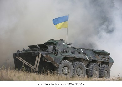 ZHYTOMYR, UKRAINE - AUGUST, 11, 2015: Ukrainian soldiers on an armored personnel carrier take part in the training at the military training ground near Zhytomyr