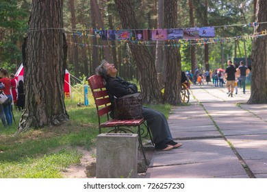 Zhytomyr, Ukraine - May 05, 2015: Homless old woman sleep on the bench at park