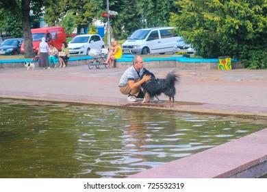 Zhytomyr, Ukraine - September 05, 2015: dog licks the man near river at park