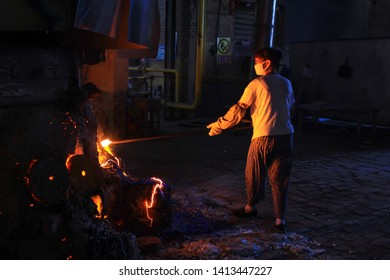 Zibo,Shandong ,China-July,25,2018:A womam worker takes glaze from a raw material smelting furnace in Glass Crafts Factory at Zichuan,Zibo,China