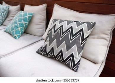 Zigzag pattern cushions on the outdoor seating with timber background