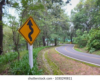 Zigzag warning signs beside a downhill sharp curve in Chiang Mai,Thailand. Horizontal shot.