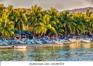 Zihuatanejo, Mexico. Circa October 2009. Small fishing boats return to the beach at sunset and sell their catch to local restaurants.