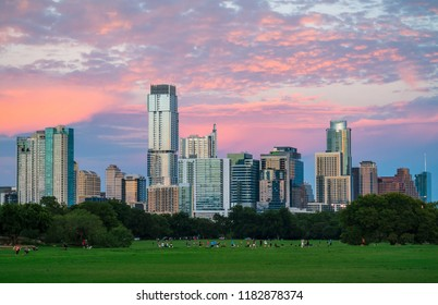 Zilker Park Sunset in Austin , Texas , USA pink clouds light up the sky at the Perfect Sunset in the big green grass park in the amazing Texas Capital City Skyline Cityscape glows golden hour