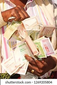 Zimbabwe money being held and handled