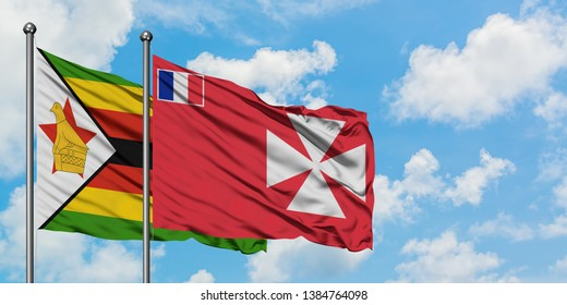 Zimbabwe and Wallis And Futuna flag waving in the wind against white cloudy blue sky together. Diplomacy concept, international relations.