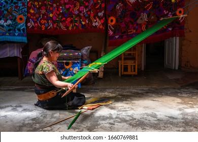 ZINACANTAN, MEXICO - MARCH 1, 2020: A Tzotzil Mayan woman weaving a textile with the back strap loom technique in the region of San Cristobal de las Casas, Chiapas state.