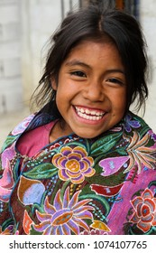 Zinacantan, Mexico - November 8, 2013: A young indigenous Tzotzil Maya girl smiling outside her home in a rural village near San Cristobal de la Casas in the Chiapas state.
