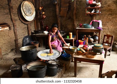 Zinacantan; United Mexican States - may 15 2018 : a woman is cooking tortillas in an Indian kitchen