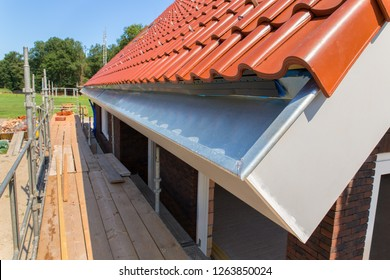 Zinc rain gutter with roof tiles and scaffolding at new house
