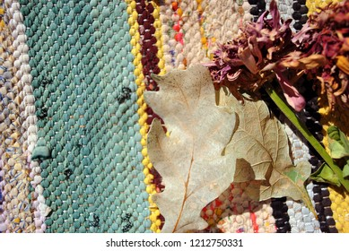 Zinnia bicolor flaccid flowers and white oak leaves on folk style carpet of the 19th century striped colorful background,  close up detail