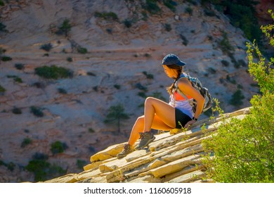 ZION, UTAH, USA - JUNE 12, 2018: Outdoor beautiful view of young woman with beautiful scenery in Zion National Park along the Angel's Landing trail, Hiking in Zion Canyon, Utah