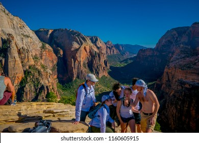 ZION, UTAH, USA - JUNE 14, 2018: Outdoor beautiful view of young hikers looking at view in Zion National park. People living healthy active lifestyle in Zion Canyon, Utah