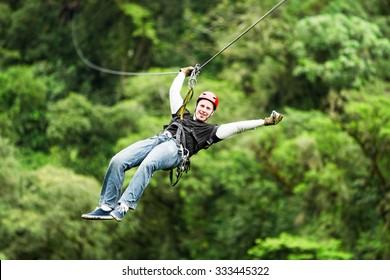 zipline canopy zip line wire adventure jungle forest sport flight adult male mountaineer wearing informal clothing on zipline or canopi experience in ecuadorian rain forest zipline canopy zip line wir