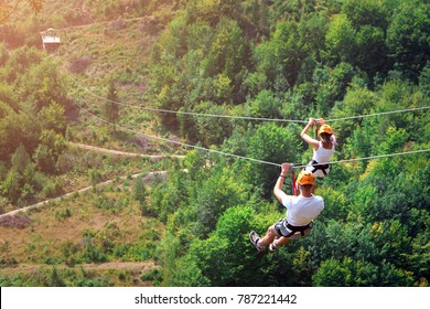 Zipline is an exciting adventure activity. Man and woman hanging on a rope-way. Tourists ride on the Zipline through the canyon of the Tara River Montenegro. Couple in helmets is riding on a cable car
