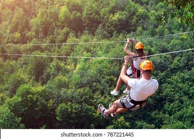 Zipline es una emocionante actividad de aventura. Hombre y mujer colgando de una cuerda. Turistas recorren el Zipline a través del cañón del río Tara Montenegro. Pareja de cascos montada en un teleférico