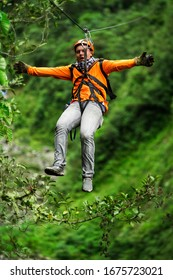 ziplining jungle zip line man adult adult tourist on zipline dressed in orange against green background ziplining jungle zip line man adult tour sport zipline canopi vacation vegetation canopy outdoor