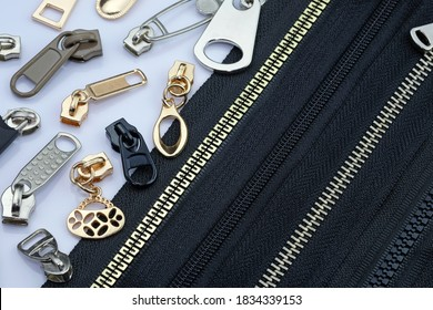 Zipper on a black fabric base with different color runners. different types of metal zipper slider for zipper. Gold, silver chrome runners 				 for sewing clothes with a zipper