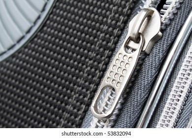 A zipper on the grayish suitcase closeup photo