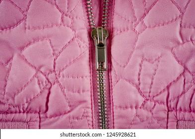Zipper on pink balon jacket close-up shot.