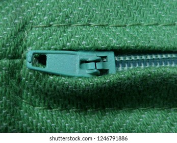 zipper puller macro or close up with green wool fabric material and fine stitching