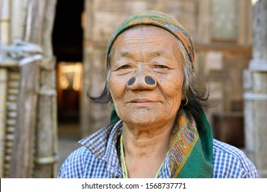 Ziro valley, Arunachal Pradesh, India - 08 JANUARY 2019: Apatani woman in front of the house with tribal face tattoo and black wooden nose plugs, to make them less appealin