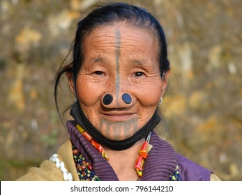 ZIRO VALLEY, ARUNACHAL PRADESH, INDIA - OCT 24, 2017: Old Apatani woman with tribal face tattoo and traditional wooden nose plugs poses for the camera in Ziro Valley, on Oct 24, 2017.