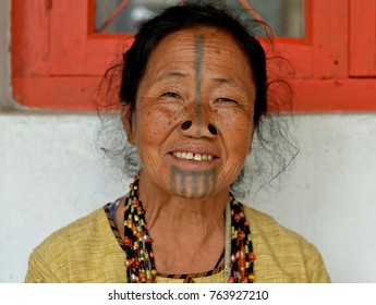 Ziro Valley, Arunachal Pradesh/Northeast India - Oct 22, 2017: Elderly Apatani tribal woman with black wooden nose plugs and distinctive tribal face tattoo poses for the camera, on Oct 22, 2017.