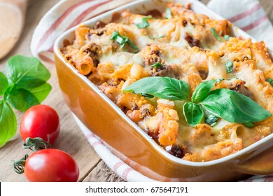 Ziti bolognese in baking dish, pasta casserole with minced meat, tomato sauce and cheese, horizontal