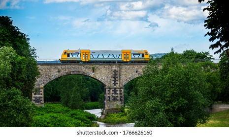 "Zittau, Saxony / Germany - June 30th 2020. Train of ""trilex"" (Laenderbahn GmbH) driving over the railway viaduct crossing river Neisse near Zittau at the German - Czech border"