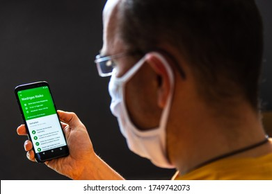 Zittau, Saxony / Germany, June 5th 2020: Young man wearing a protective face mask checks the German corona warn app for his infection risk analysis. Niedriges Risiko = German for Low Risk, Shallow DOF