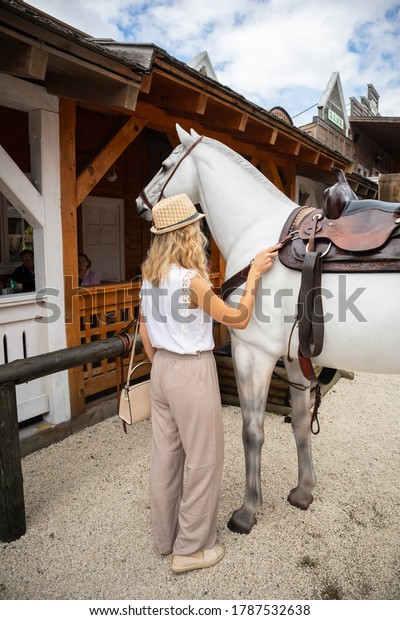 Zlatibor, Vodice, Serbia - July 26. 2020 Woman and model of a wooden horse on in the city of El Paso in wild west style and cowboy style. Western thematic park. Travel concept