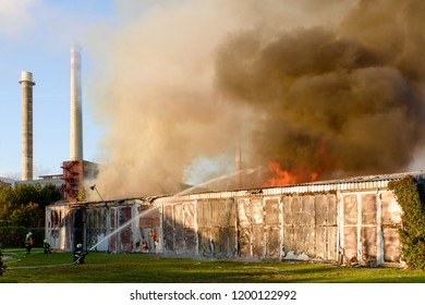 ZLIN, CZECH REPUBLIC, 10-05-2018: Fire of the warehouse in Zlin, Czech Republic. Fire brigades intervenes in the location. Fire and smoke is seen above the warehouse.