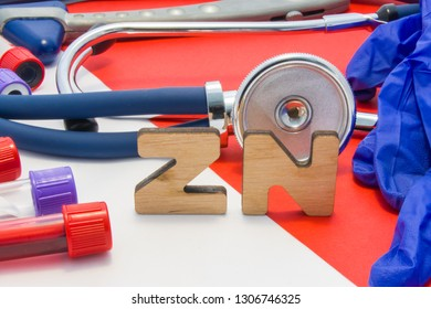 ZN medical abbreviation meaning total zinc in body or blood in laboratory diagnostics on red background. Chemical name of ZN is surrounded by medical laboratory test tubes with blood, stethoscope