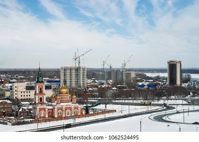 Znamensky temple against backdrop of build buildings. Golden domes. Cityscape of Barnaul with church and high-rise buildings, shot from height, 28 March 2018. Barnaul, Russia. View from upland park