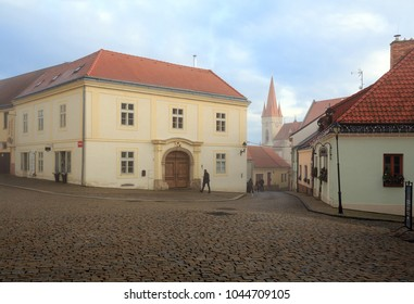 ZNOJMO, CZECH REPUBLIC - DECEMBER 28, 2017. Cobbled street in the historical downtown on a foggy winter day. View of the St. Nicholas Church. Znojmo, Czech Republic, Europe