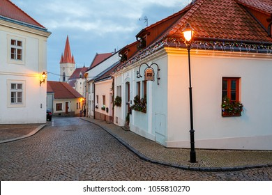 ZNOJMO, CZECH REPUBLIC - DECEMBER 28, 2017. Cobbled street in the historical downtown on a winter evening. View of the St. Nicholas Church. Znojmo, Czech Republic, South Moravia, Europe