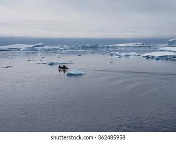 Zodiac in Antarctica blue iceberg landscape ocean mirrow reflection