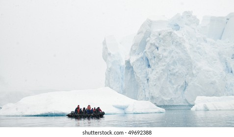 A zodiac boat filled with people looking at a massive iceberg in a snow storm - Antarctica