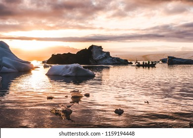 Zodiac boat sailing in Glacier lagoon Jokulsarlon sunset between icebergs pieces of ice clouds sky reflecting on the water in Iceland