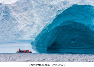 Zodiac in front of enormous ice berg in Antarctica