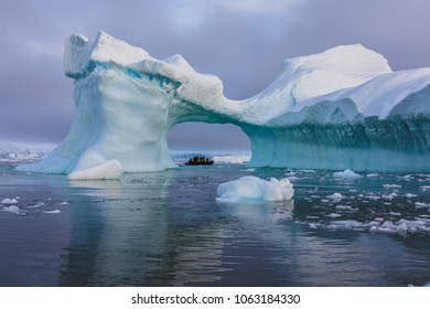 A zodiac full of tourist viewed through an arch in a large blue iceberg with reflections, Antarctica