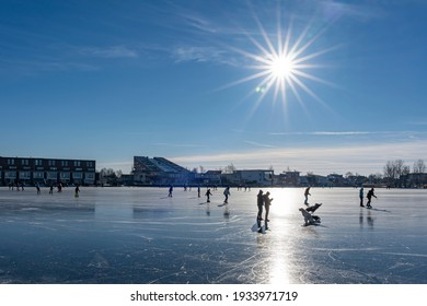 Zoetermeer, Netherlands - 02-13-2021; During this beautiful sunny winter day, many people are ice skating on this lake in Zoetermeer