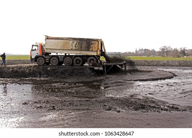 Zoeterwoude, Netherlands - February 7, 2011: large truck with tipper trailer unloads its freight of dredging spoil (sludge, sediment) into a storage compartment (depot)