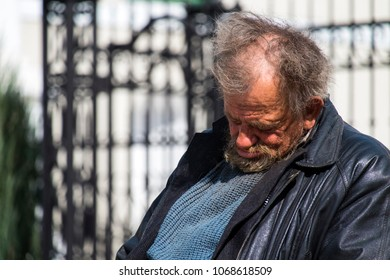 Zolochiv, Ukraine - April 10, 2018: Homeless tramp sitting asleep on a bench in the city center along Markian Shashkevich Street, near the Church of the Resurrection of the Lord