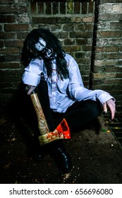A zombie girl with a ax with a lot of blood sitting against a stone wall