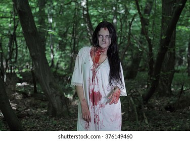 Zombie girl with her throat cut in a blood-stained white shirt in the forest.