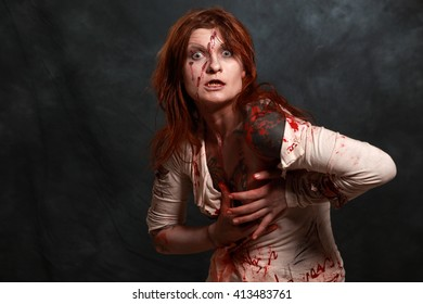 Zombie girl. Studio photo of young girl in zombie make-up and costume taken against dark grey fabric background